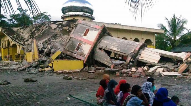 ejumlah warga berkumpul di luar sebuah masjid yang mengalami kerusakan akibat gempa yang mengguncang Kabupaten Pidie Jaya, Aceh, Rabu (7/12). Seperti dirilis BMKG, gempa berkekuatan 6,4 SR mengguncang Aceh sekitar pukul 05.03 WIB. (Zian Muttaqien/AFP)
