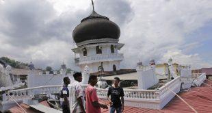 Warga memeriksa sebuah masjid yang amblas karena gempa di Pidie Jaya, Aceh (7/12). (AP/Heri Juanda)